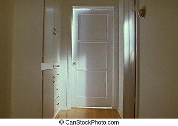 Dolly down hallway to closed door