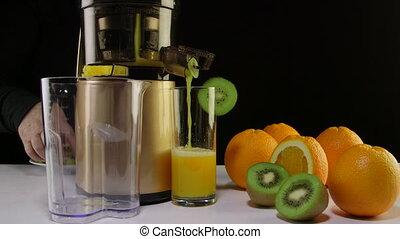 Dolly: Making fresh fruit juice from orange and kiwi using masticating juicer machine