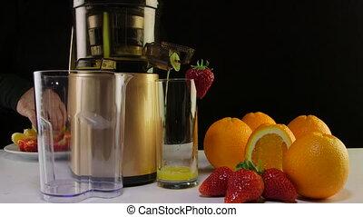 Dolly: Making fresh fruit juice from strawberry and orange using masticating juicer