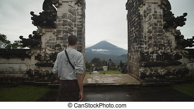 Dolly medium shot of a man walking towards Gates of Heaven temple gates in Pura Penataran Agung Lempuyang temple in Bali with reveal of the Mount Agung volcano and temple grounds below 4K