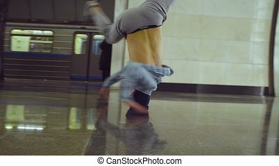Brakedance. Young man dancing on the subway station