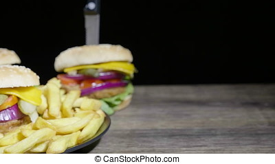 Dolly shot. Delicous home made hamburger with fries on wooden table
