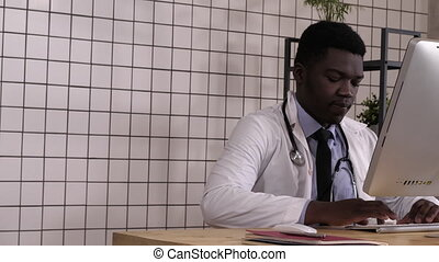 Dolly shot. Entering african male doctor sitting down at desk and start working. Professional shot in 4K resolution. 017. You can use it e.g. in your commercial video, medical, business, presentation, broadcast