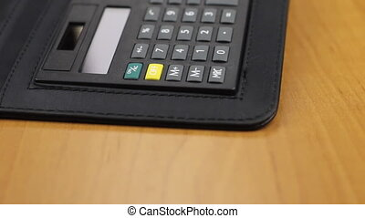 Dolly shot, focus on a calculator and diary lying on a...