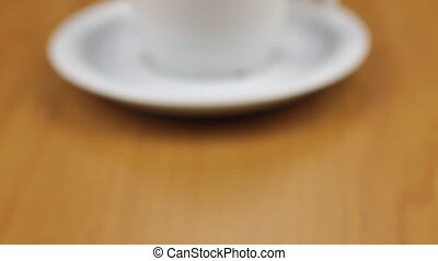 Dolly shot, focus on a cup of freshly brewed coffee standing on a table.