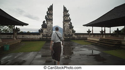 Dolly shot following a white male tourist walking towards a famous black stone pillars in Pura Penataran Agung Lempuyang temple in Bali with Mount Agung volcano in the background. 4K