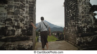 Dolly shot following a white male tourist walking towards a famous Gates of Heaven in Pura Penataran Agung Lempuyang temple in Bali with reveal of the Mount Agung volcano and temple grounds 4K