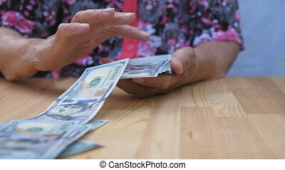 Dolly shot hands of elderly grandmother holds bundle of money and scatters foreign currency on the desk. Arms of old granny throws one hundred dollar bills on the table in front to camera. Slow motion