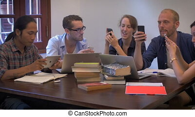 Dolly shot of 5 young workers all checking their smart phones at a meeting