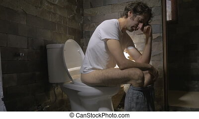 Dolly shot of a man sitting on a toilet feeling ill, depressed, or upset