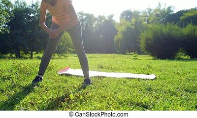 Dolly shot of a nice aged woamn doign sport exercises outdoors