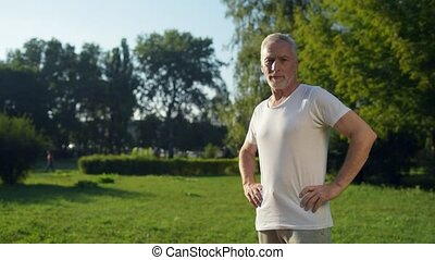 Dolly shot of a sporty aged man standing in the park