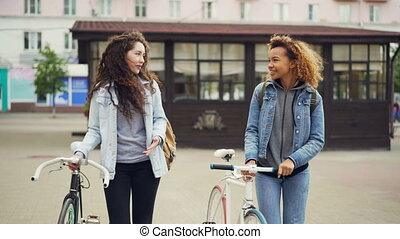 Dolly shot of attractive girls friends walking with bicycles...