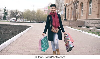 Dolly shot of Attractive mixed race girl dancing and have fun while walking down the street with bags. Happy young woman walking after shopping on mall sale