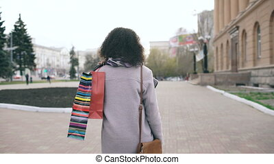 Dolly shot of Attractive mixed race girl turning around with shopping bags and smiling into camera . Young woman walking after mall sale