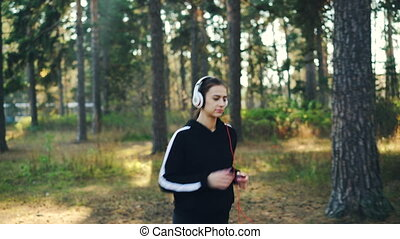 Dolly shot of attractive woman jogging in park and listening...