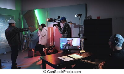 Dolly shot of Backstage of thriller film shooting: black man trying to shoot young black woman.