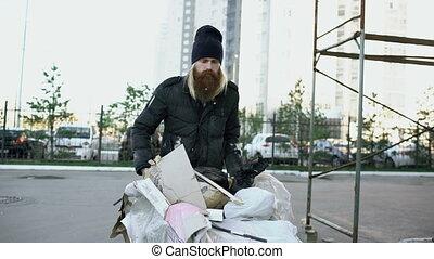 Dolly shot of Bearded homeless man walking down the street...
