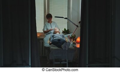 Dolly shot of Beautician making relaxing facial massage with jade roller on woman's face at beauty salon with dim light around and pleasant atmosphere.