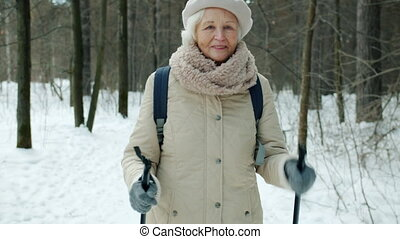 Dolly shot of beautiful senior sportswoman enjoying nordic walking in winter park watching nature looking around. Retirement and sports concept.