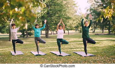 Dolly shot of beautiful women yogini standing on yoga mats in Tree pose with arms raised in Namaste during yoga class in park. Youth and nature concept.