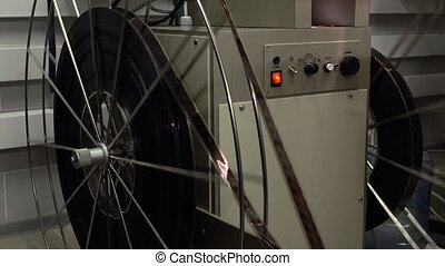 Dolly shot of big rotating reels in pro cinema projector, 4K video, part of set