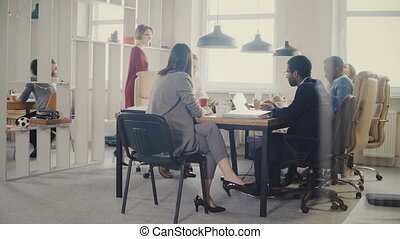 Dolly shot of business people brainstorming at modern office meeting. Happy creative multiethnic staff discussion 4K.