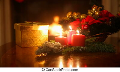 Dolly shot of candles and Christmas gift on table at living...