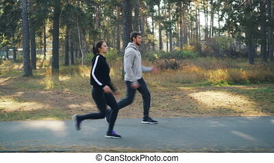 Dolly shot of cheerful friends woman and man running and...
