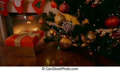 Dolly shot of Christmas present in red box with golden bow at living room with burning fireplace