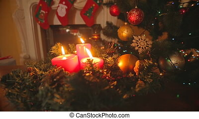 Dolly shot of Christmas wreath with burning red candles on...