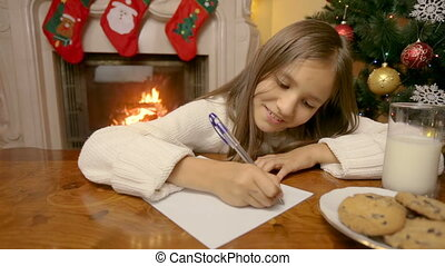 Dolly shot of cute girl in white sweater writing letter to Santa Claus at living room by the fireplace