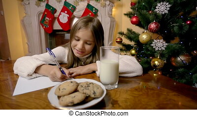 Dolly shot of cute girl writing letter to santa at living room with fireplace