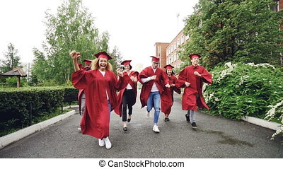 Dolly shot of excited grads running on campus wearing gowns...