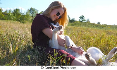 Dolly shot of girl in sunglasses sitting on grass at meadow...