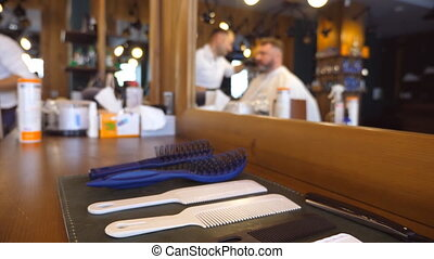 Dolly shot of hairdressers tools at table. Accessories and...