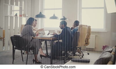 Dolly shot of happy business partners discussion in modern office. Multiethnic bosses collaborate on business project 4K