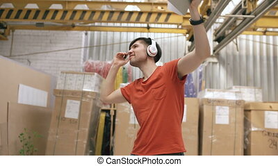 Dolly shot of Happy young worker in industrial warehouse listening to music and dancing during work. Man in headphones have fun at workplace.
