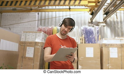 Dolly shot of Happy young worker in industrial warehouse...