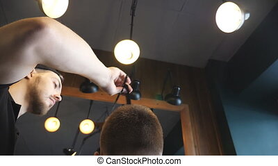 Dolly shot of male hairdresser combing hair of his customer...