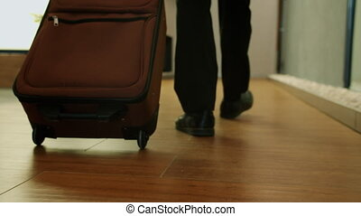 Dolly shot of male legs walking in hotel hall with suitcase while man is travelling alone enjoying new accommodation. Tourism and travellers concept.