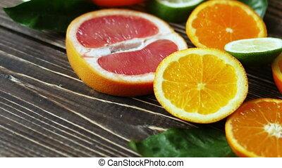Dolly shot of orange, lime, grapefruit slices on wooden table. 4k