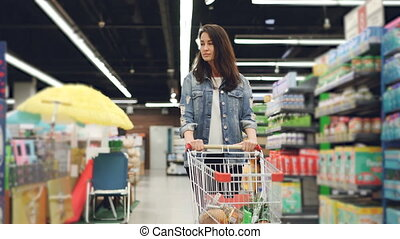 Dolly shot of pretty young lady with shopping cart walking...