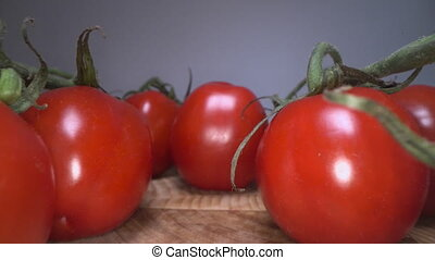 Dolly shot of red cheery tomatoes on top of wooden table...