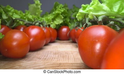 Dolly shot of red cheery tomatoes with lettuce leafs on top...