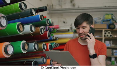 Dolly shot of smiling worker in warehouse talking smartphone and checking inventory. Man works in sales department of advertising materials