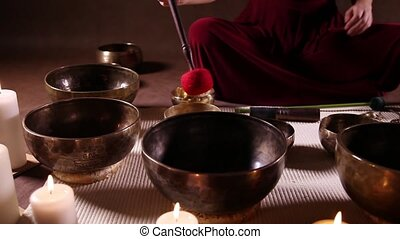 Dolly shot of Tibetan singing bowls - Woman playing Tibetan...