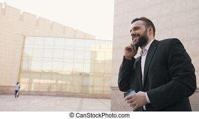 Dolly shot of young bearded business man talking at smartphone with cup of coffee near modern office buildings