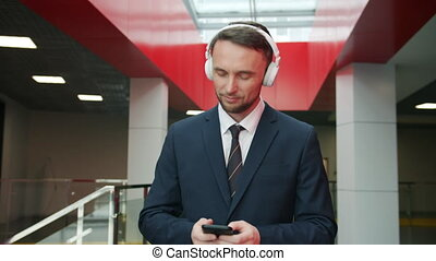 Dolly shot of young businessman listening to music in ...