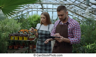 Dolly shot of Young couple florists work in garden center. Attractive man and woman count flowers using tablet computer during working in greenhouse